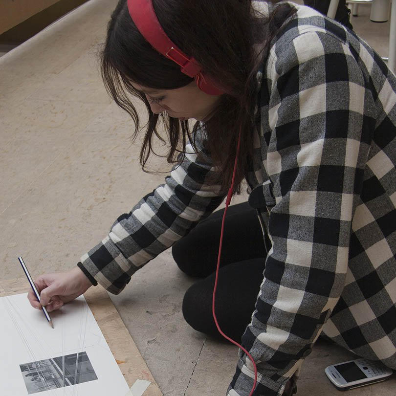 Alumna dibujando sentada en el suelo