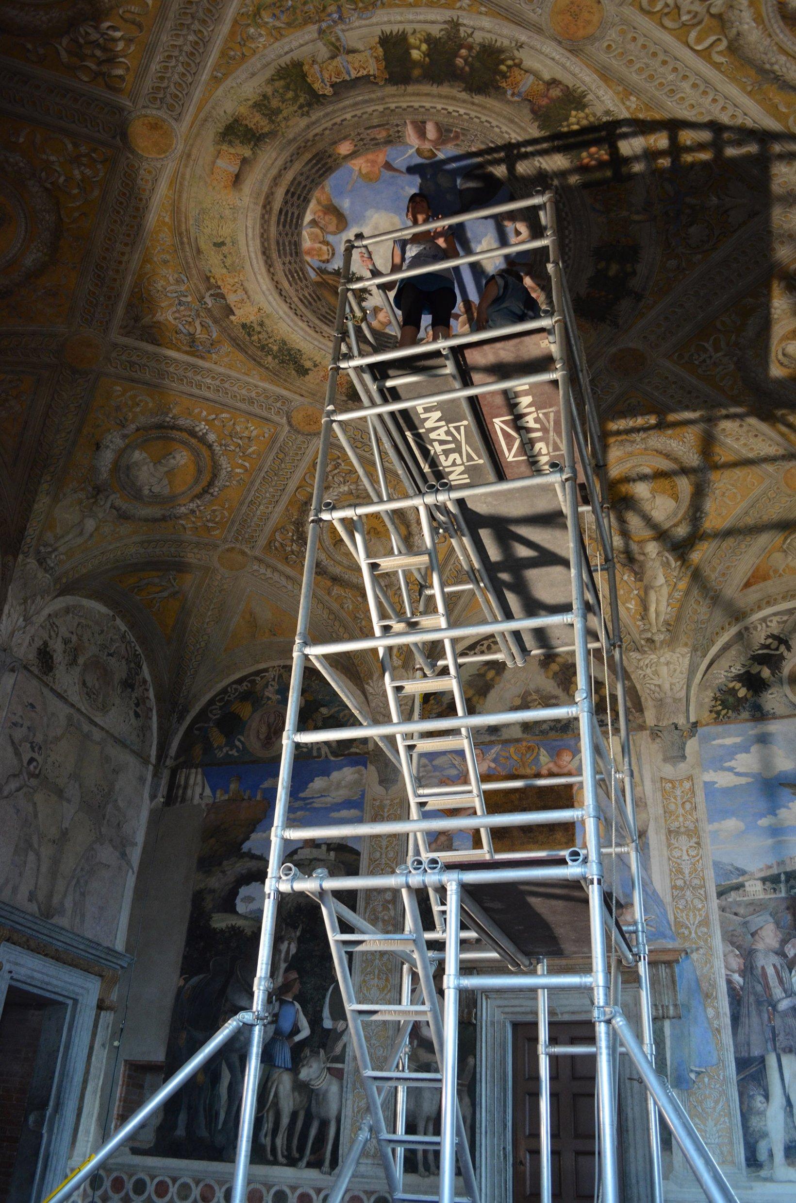 Vista desde el suelo de una de las alumnas sobre un andamio listo para la restauración de la pintura mural del techo (Camera degli Sposi)