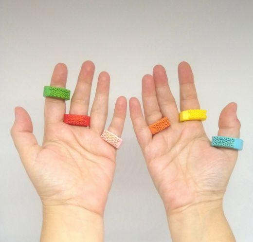 Primer plano de las palmas de las manos de una usuaria con tres anillos en cada mano