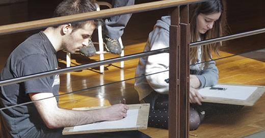 Dos alumnos dibujan sentados en el suelo