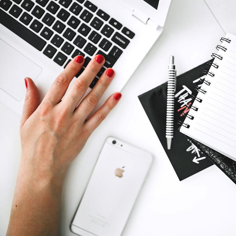 Vista superior de mano femenina sobre un portátil, teléfono móvil, agenda y bolígrafo