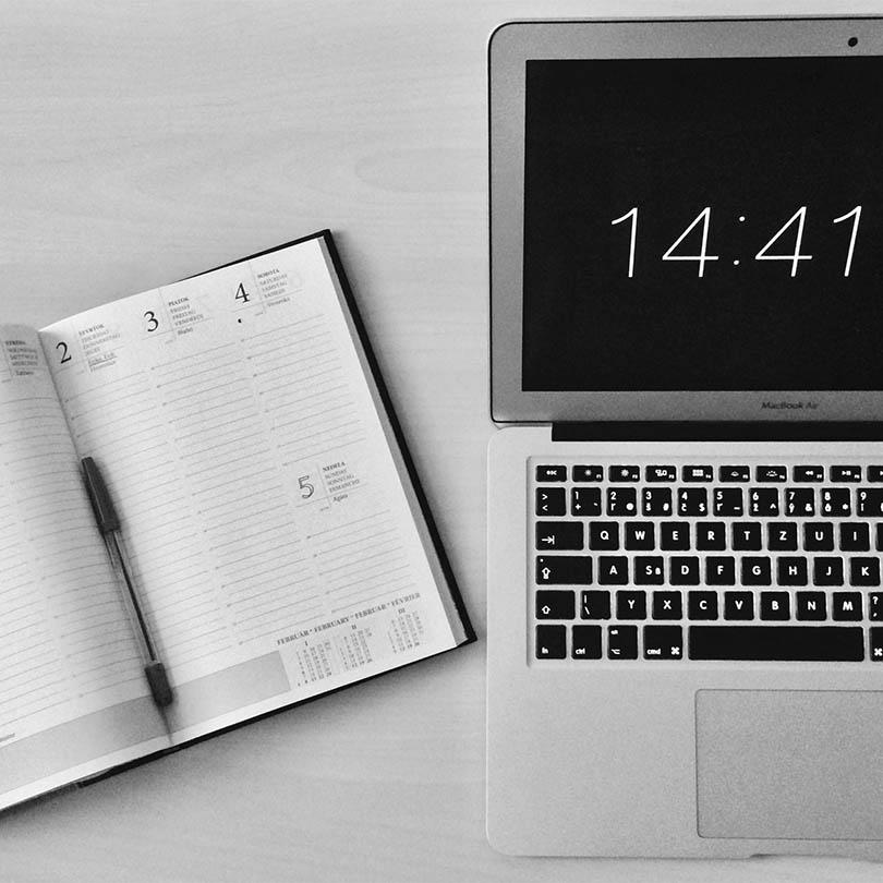 Portátil y agenda abierta con un bolígrafo sobre sus páginas