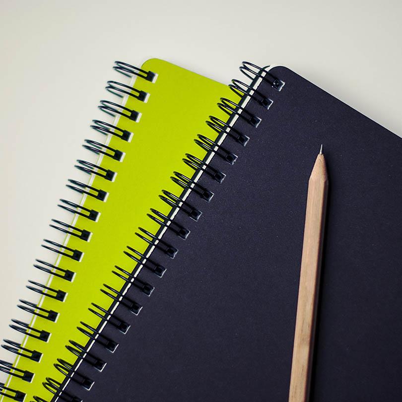 Dos blocs de notas con un lapicero encima