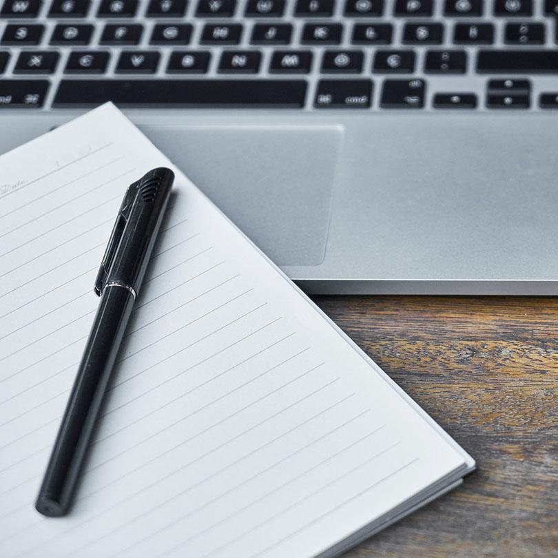 Vista parcial de una libreta, una pluma y un portátil