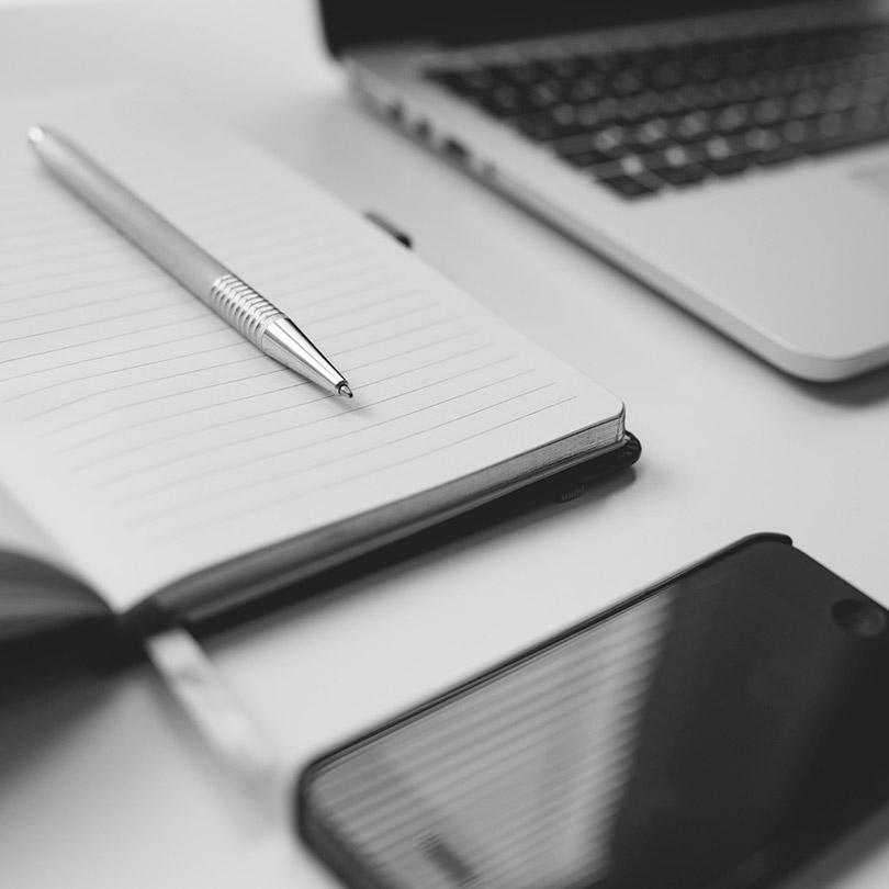 Vista parcial de una agenda, un bolígrafo, un móvil y un portátil