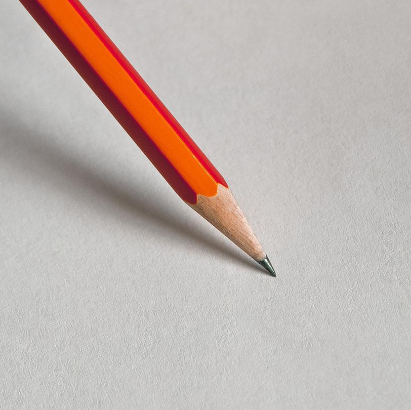 Lapicero naranja con la punta apoyada sobre un papel en blanco