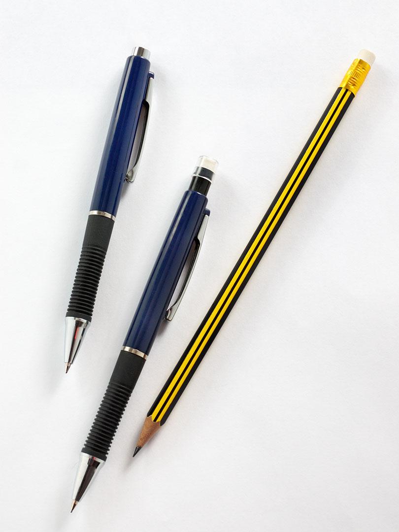 Un bolígrafo, un portaminas y un lápiz sobre una superficie blanca